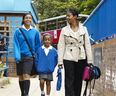 Mother and two daughters walking to school.