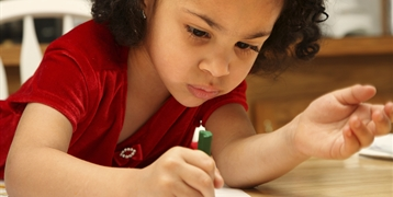 A young girl colouring with a crayon.