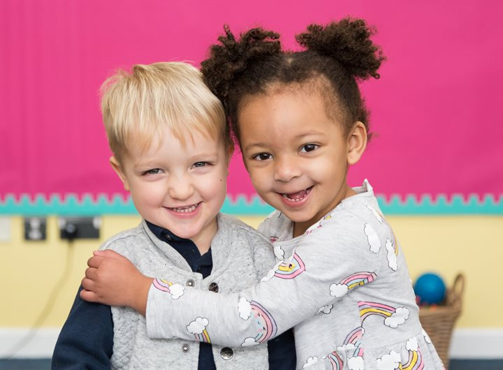 two young children smiling hugging