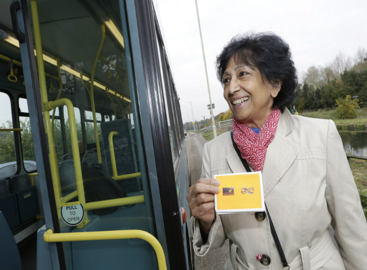 A woman getting on a bus, showing the driver a travel wallet