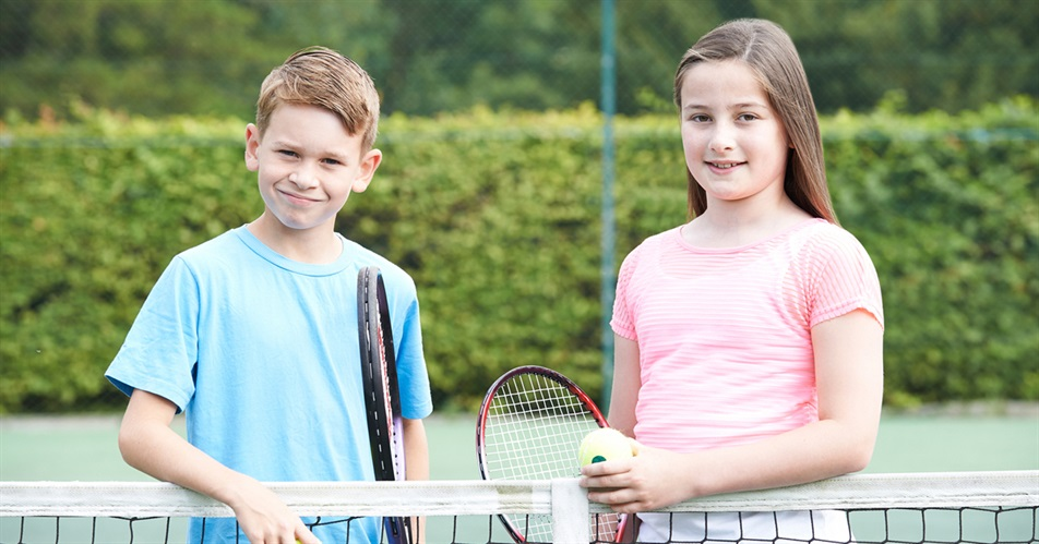A boy and girl playing tennis.