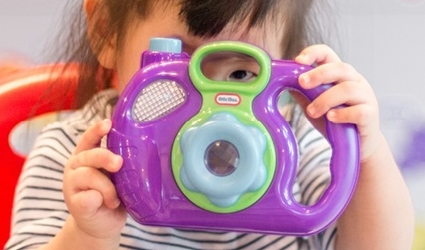 A toddler holding a toy camera