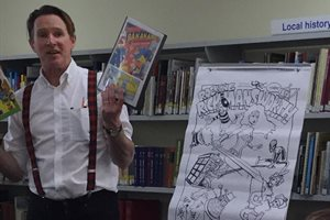 Kev F Sutherland with comic cover at Rickmansworth Library
