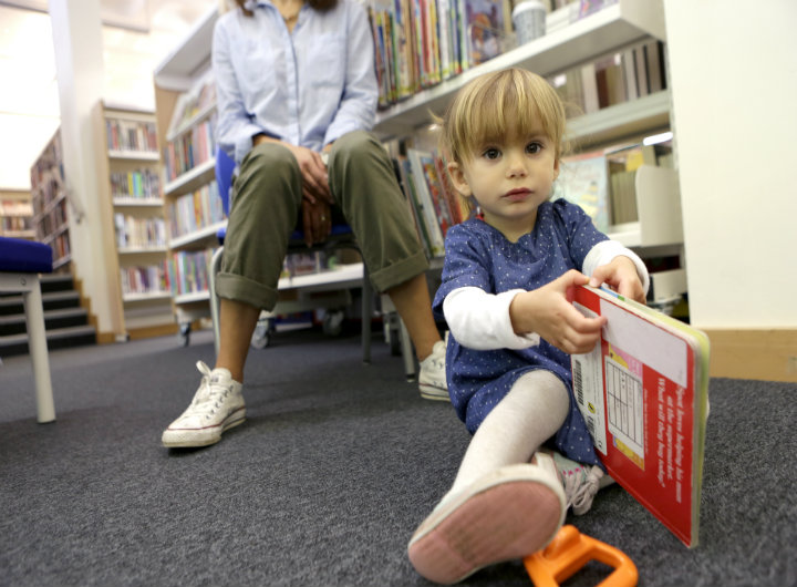 A little girl reading a book in a library
