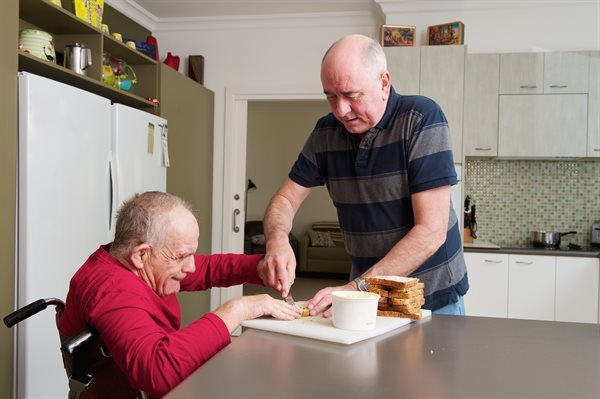 Home carer assisting man with disability
