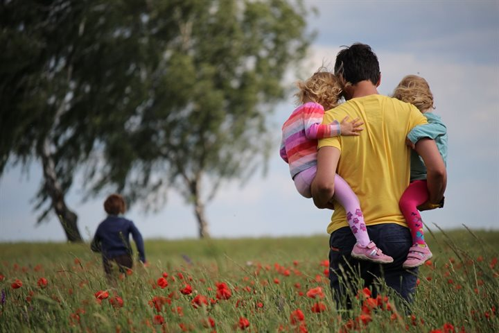 Dad and 3 kids walking in a field