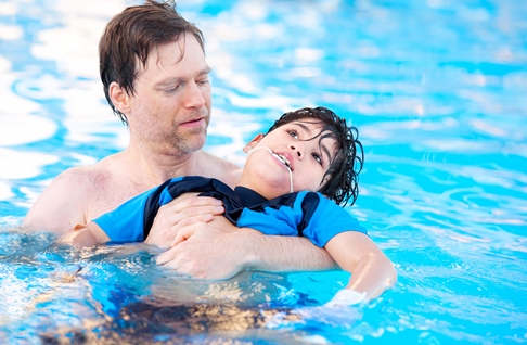 Father swimming in pool with child