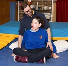A man and a teenager with special educational needs on a trampoline.
